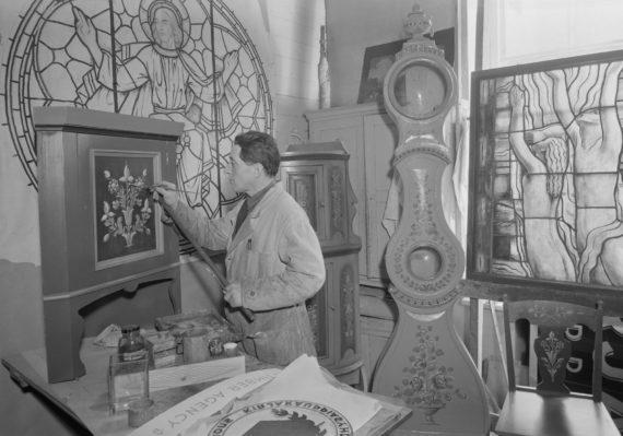 Taiteilija Fritz Hilbert koristelee seinäkaappia