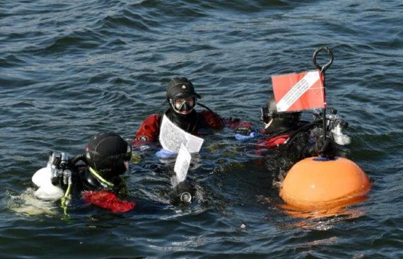 Sukeltajat lähdössä hylkypuiston sukellusreitille kartat käsissään